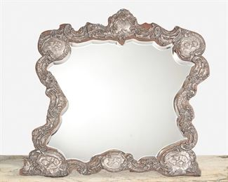 """289 An English Sterling Silver Repousse Dressing Table Mirror 1904; Birmingham, England Marked for Birmingham; Further marked: JM & Co. [possibly Joseph Moore] The dressing table mirror with sterling silver repousse overlay with scrolling foliage, rocaille, and putti with monogrammed central cartouche on wooden easel-back frame enclosing a beveled mirror 24"""" H x 25"""" W x 14"""" D Estimate: $1,000 - $1,500"""