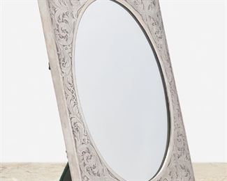 """290 An American Sterling Silver Framed Table Mirror First-half 20th Century Marked for William B. Kerr & Co.; Further marked: Sterling / 3481 The rectangular sterling silver easel-back frame with scrolling foliate motif and cartouche to bottom enclosing an oval mirror 18"""" H x 14.75"""" W x 6.75"""" D 29.3 oz. troy approximately Estimate: $600 - $800"""