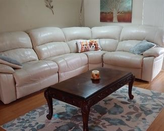Leather Sectional with Recliners, Area Rug & Coffee Table. Artwork, Wall Art.  Contemporary Floor Lamp that curves out from the back of the couch