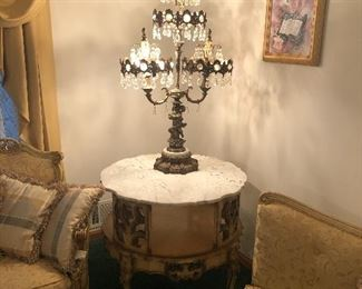 Unique brass lamp adorned with crystals and cherubs atop beautiful Italian-made end table with marble top.