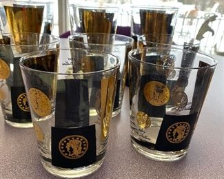 """Mid Century/Hollywood Regency Bar Ware by Cera. Gold and black """"money"""" graphic adorn these awesome vintage glasses.  Some minor paint loss.  These amazing glasses each measure about 4.4"""" tall."""