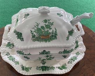 """This tureen is an oblong octagonal shape with a handled lid, floral embossed handles, and four feet on the base. The body and lid of the tureen are decorated with a design depicting a basket of green flowers and plants. This tureen comes with a matching underplate and both pieces are marked """"Spode Copeland China England"""". The underplate measures 15"""" x 11.5"""""""
