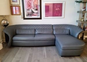 """Amazing Grey Italian Leather Sofa by Kelvin Giormani. Truly stunning piece of furniture that was recently purchased and in excellent condition! The sofa measures 120"""" wide and the chaise is 66"""" deep. Please note that winning bidder is responsible for providing their own assistance moving this item and the pickup is at a different location."""