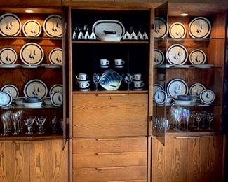 Lighted display cabinet full of Noritake stoneware sailboat dishes and glassware