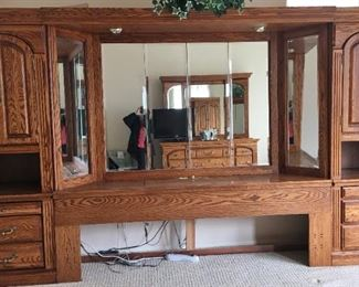 """Michael Howard Georgian Court Wall Bed Unit. King headboard with hutch, 2 pier cabinets on either side. Headboard has center storage with lighted lift lid, outlets, phone jack; hutch with 3 panel beveled tri fold mirror, overhead lighting. Approx 11' wide, 77"""" high."""
