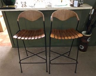 Arthur Umanoff for Raymor. Set of 2 wrought iron and sculptural rush back barstools with maple slat seats. Mid Century.
