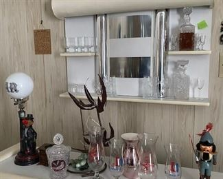 Bar with chairs, glassware, bar lamp.
