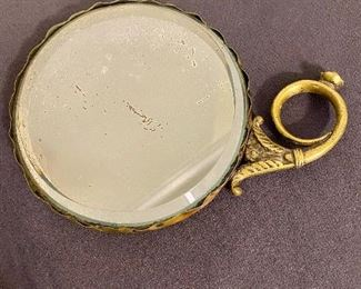 Additional photo of hand mirror. Beveled glass with scaloped metal edges.