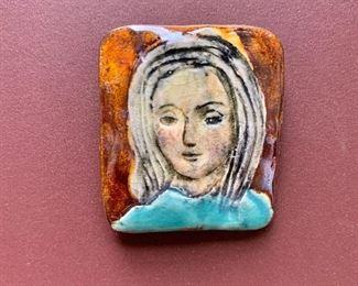 """$30 - Glazed ceramic portrait pin; 1.5"""" H x 1.25"""" W"""
