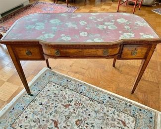 "$475 -Louis XVI style writing desk with 3 drawers, brass ring pulls; fabric panel under safety glass; band inlay, raised on brass capped feet and casters; 30"" H x 49"" W x 23.5"" D"