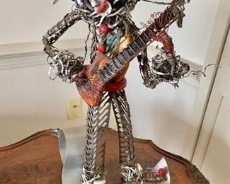 "$250 - Dragutin Fradl signed folk art mixed metal guitar player; 18"" H x 12"" D x 9"" W"