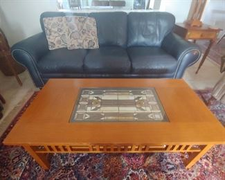Navy Blue Leather Sofa with stud accents and Mission Style Coffee Table with Stained Glass Insert.  Karastan Rug