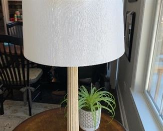 "Lot 5508  $44.00. 30"" H  Columnar Table Lamp in a Textured Cream Color Furnish. 15"" Diameter Shade. Paired with a Faux plant in Pottery Pot."