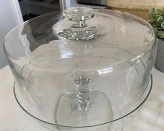 """Lot 5547.  $40.00  14"""" diam glass cake plate and a dome-covered pedestal cake plate (tiny chip on edge of pedestal plate.)"""