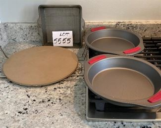 """Lot 5555.   $35.00   This lot features a """"like new"""" 13"""" Pampered Chef pizza stone and two metal carrying racks; 2 Food Network Pie Pans and an 8"""" square metal dish."""