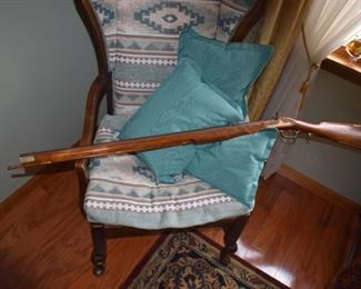 Wing back chair with Long black powder rifle, This Rifle is Still available  284.00.   !!!!!