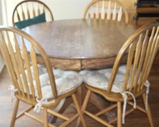 Round oak table with claw feet and oak chairs.