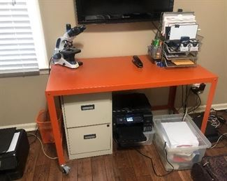 A metal orange desk on rollers. $20