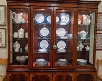 Banded mahogany two-piece lighted china cabinet, with beveled glass, various sets of porcelain and china within.