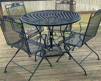Wrought iron patio set with four rocking chairs.