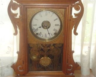 Dining Room:  This antique oak kitchen clock has a gold design on its glass door which opens from the left.