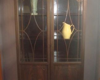 """Dining Room:  A china hutch has three interior shelves behind two upper glass doors as well as two lower doors. The hutch measures 38"""" wide x 14"""" deep x 78"""" tall. Two of the interior shelves are adjustable.  The key will be with cashier. The turquoise McCoy vase and yellow ceramic pitcher are also for sale."""
