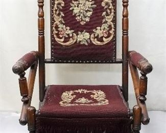 """$175 - Late Victorian platform rocker, dark wood with many turnings, casters on front feet, needlepoint upholstery on back, front & arms.  Measurements: 22.5""""W x 45""""H x 26""""Diameter; 15"""" (seat height)   Condition: Good, but there is some wear in the needlepoint seat. Two small squares of glowtape on one side, which could be removed with care."""