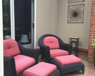 Three-piece black wicker set with cushions, plus Metal wall hangings.