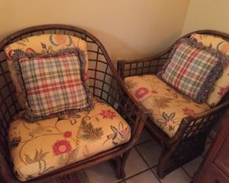 Matching rattan chair with cushions and pillows.