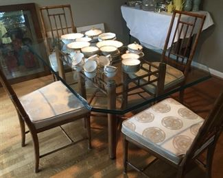 Rattan style table with glass top and four upholstered chairs.