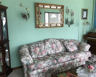 Floral sofa, brass decor, mirror, upright piano with bench