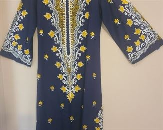 Handcrafted dress from Egypt. Amazing beautiful embroidery stitching all over the dress. The size is a 46. Dress is a dark blue with white, yellow, green and silver stitching. Dress has been in the family since 1942 and is still in good condition, but there is a small hole in sleeve. Dress is made of a thick material with bell sleeves and the zipper works still. https://ctbids.com/#!/description/share/821787