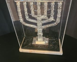 "Sterling silver menorah on a two-tier platform with a thick plastic cover. Menorah was crafted in Israel and given to the woman's husband when they helped build a church in Israel. There are etchings of scenes and Hebrew quotes in the menorah. Measures 10 "" x 5"" x 13"" with casing. The menorah measurements are 8"" x 2"" x 10"". Stamped 925. https://ctbids.com/#!/description/share/821781"