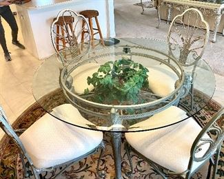 "2-	Glass top and iron base table 54""D x 29""H with four chairs 	$295"