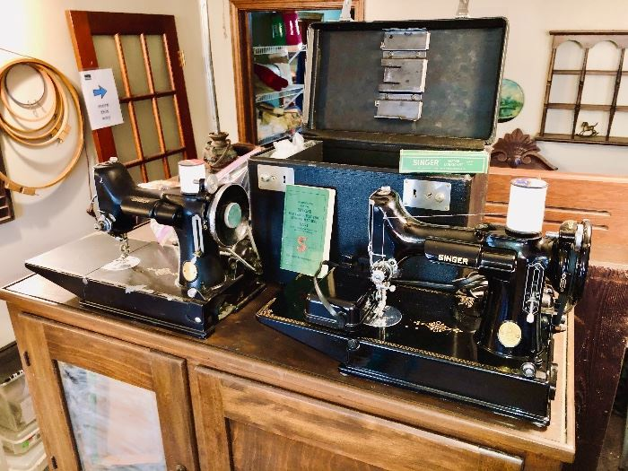 TWO Singer Featherweight sewing machines!  Model 221-1.  The unit on the right comes complete with case, manual, lubricant, foot pedal and other accessories.  The left unit comes with only its foot pedal.