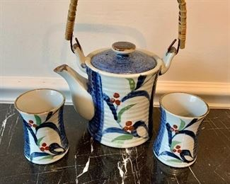 $50 - Tea set with pot and two cups; 9 in. H teapot with handle up x 7 1/2 in. W. Each cup is 3 in. H