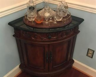 One of a pair of corner cabinets and crystal decanters, a Waterford decanter