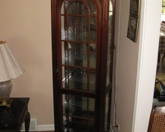 Lighted cherry curio cabinet having glass shelves