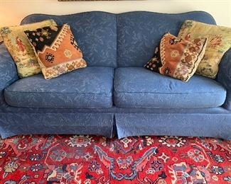 Nicely upholstered blue sofa in pristine condition