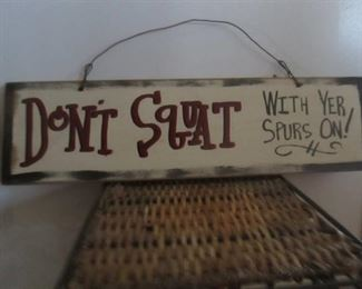 "Wood sign ""Don't squat with yer spurs on""   5 1/2"" x 20"""