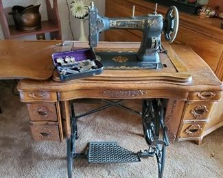 Antique White treadle sewing machine in ornate cabinet.