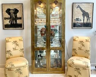 "$700 - Beautiful Brushed Gold Lighted Curio Cabinet (Minor condition issue. Some metal veneer is loose. Could be glued) - 36.5w x 15d x 85h.  $250 - Pair of custom upholstered chairs ""Palm Tree"" - 21w x 34d x 40h"