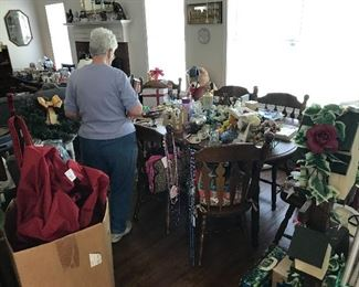 lots of collectibles displayed on table that has six chairs which is also for sale.
