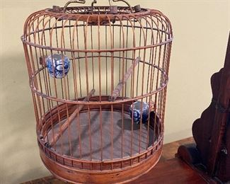 """ITEM 4: Antique Chinese birdcage on stand. Stand has intricate carvings, and a drawer. Delicate bird cage has Chinese ceramic vessels for water and food. 24.75"""" x 29.25"""" tall x 10.5"""" wide $325"""