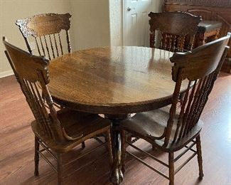 Round pedestal Paw/claw foot oak finish table and Pattern spindle back wood seat chairs.