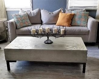 Neutral colored sofa and wooden silver gray coffee table.