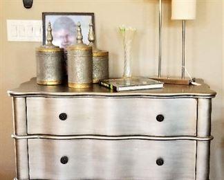 Modern silver dresser and mid-century modern lamp.