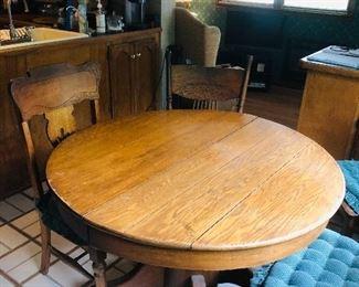 Oak pedestal table / 4 oak press back chairs