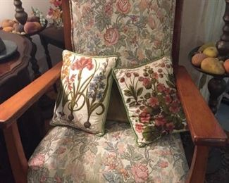 Wooden upholstered chair with crewel pillows.