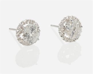 """1004 A Pair Of Diamond Halo Stud Earrings 18k white gold Each center a full-cut round diamond weighing 1.04ct and 1.22ct, and graded G-H color and I clarity, further surrounded by thirty-eight full-cut round diamonds totaling approximately 0.2ct Each: .75"""" 2.5 grams 2 pieces Estimate: $3,000 - $5,000"""